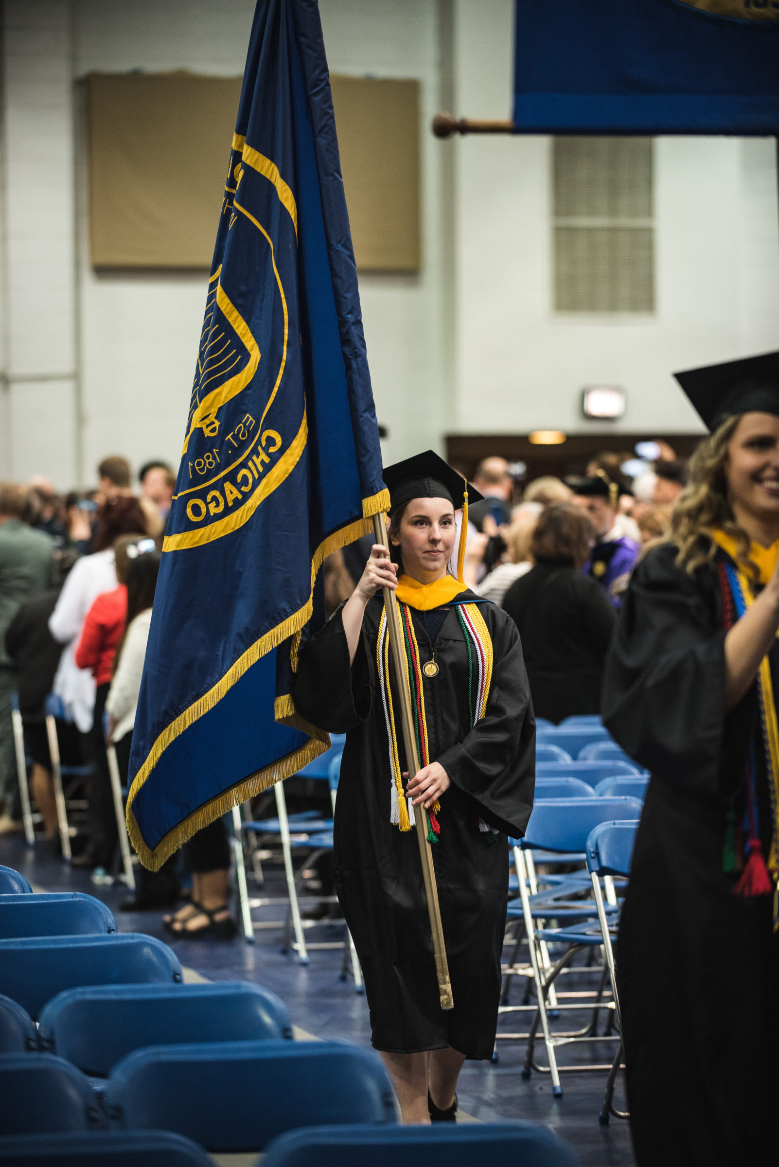 Students walking down the aisle with flags in hand.