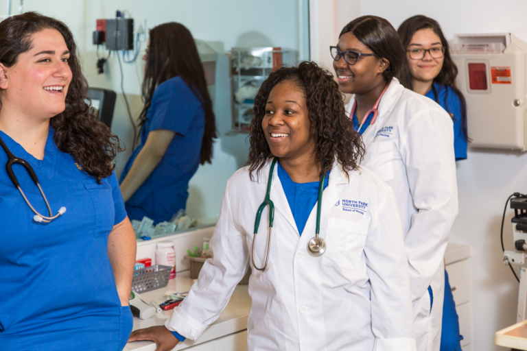 Four female nursing students in blue scrubs and white lab coats gathered in simulation lab.