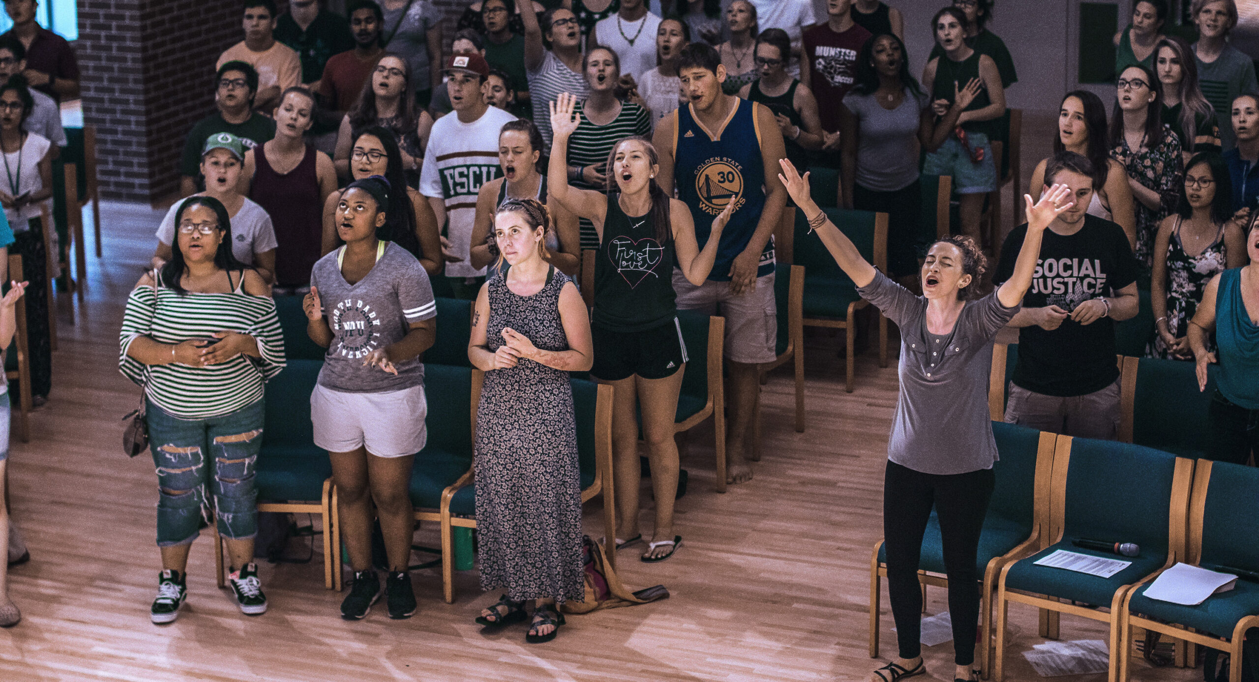 Students gathered in chapel sing and raise hands in worship.