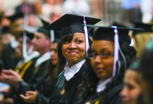 Adult graduate smiles in cap and gown at commencement ceremony